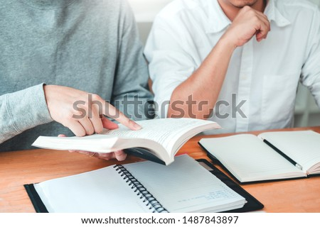 University students or college students studying and reading together in library.