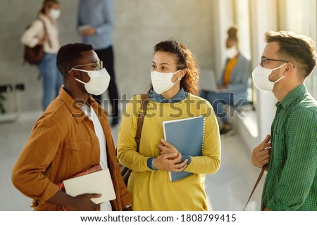 University students wearing protective face masks and communicating while standing in a hallway. Focus is on female student.