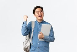 University, study abroad and lifestyle concept. Happy rejoicing asian male student with braces triumphing, pass exams, finish final semester, fist pump and shouting yes with satisfaction, hold laptop