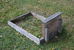 Unkempt grave with a wooden border