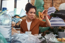 Unkempt young Asian female sitting at messy table with miserable and somber look keeping a half-eaten leftover of a fastfood