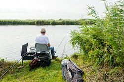 Unknown angler sitting on a chair for fishing in a small river. Around him are all kinds of accessories