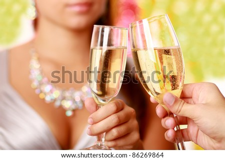 Unknown couple clinking glasses with champagne. Isolated over  christmas decorated background. Focus on champagne glasses.
