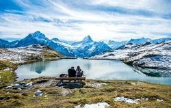 Unknown  couple on wood bench over Bachalpsee  lake landscape  above Grindelwald.