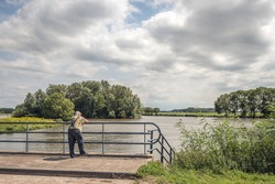 Unknown elderly man looks thoughtfully over the water of a Dutch lake while leaning on the bridge railing. He wears suspenders to hold up his blue jeans. It is a cloudy summer day.