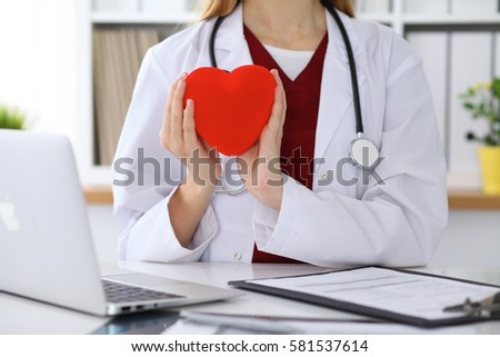 Unknown female doctor with stethoscope holding heart. Cardiology and medical care concept #581537614
