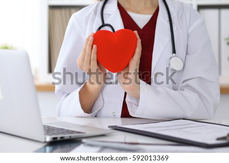 Unknown female doctor with stethoscope holding heart. Cardiology and medical care concept #592013369