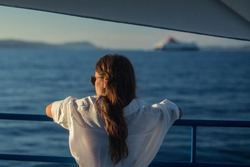 Unknown female in a white dress, long brown hair and sunglasses is enjoying the evening sun on a ferry boat. Another ferry boat is seen in the background. Travel concept.