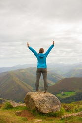 Unknown girl from the back standing on top of mountains. Pilgrim with hands up in Pyrenees mountains, France. Camino de Santiago background. Freedom and success concept. Active people concept.