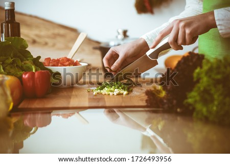 Unknown human hands cooking in kitchen. Woman slicing green onion. Healthy meal, and vegetarian food concept