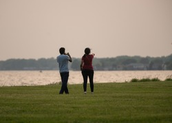 unknown Indian couple take a photo of a sunset at the park