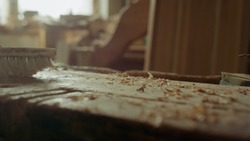Unknown man cleaning wooden surface in carpentry workshop. Unrecognized handyman sweeping table in studio. Carpenter exempting from sawdust indoors in slow motion.