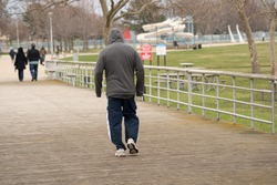 unknown man in a jogging suit takes a walk in the park