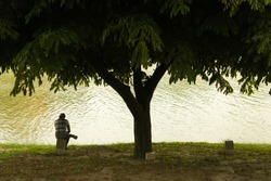 Unknown man seat under a tree in front of a lake.