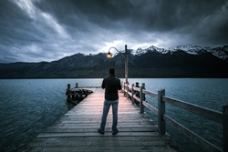 Unknown man  standing on wooden bridge by the shore of Wakatipu lake at Glenorchy in south island of Newzealand during cloudy night with dim light from light bulb on the bridge