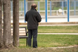 unknown man stops to read his text messages while he takes a walk