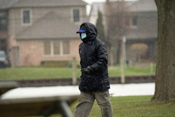 unknown man wearing a mask walks in the park during the Corona Virus