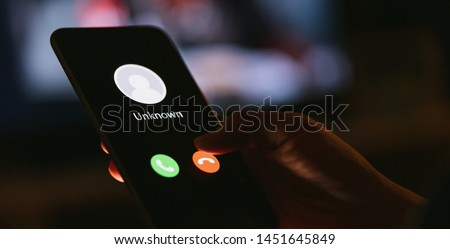 Unknown number calling in the middle of the night. Phone call from stranger. Person holding mobile and smartphone in livingroom late. Unexpected call disturbs at night.