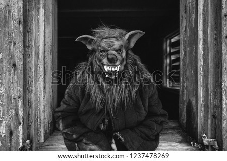 Unknown person with creepy horrible werewolf mask looking out from old wooden ghost house window. Helloween concept.  Spooky terrible fearful monster. Children fear. Frightening tales. Nightmare #1237478269