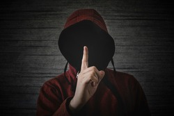 unknown person without a face in a hood shows a finger gesture meaning towns. The concept of anonymity and secrecy in the network.