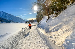 Unknown running man on the pass round the  lake Davos in winter resort Davos, Switzerland.