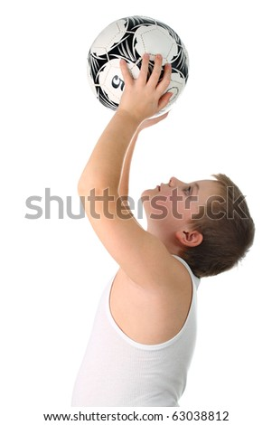 Unknown small boy holding soccer ball high above his head isolated on white