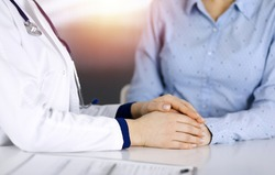 Unknown woman-doctor is holding her patient's hands to reassure a patient, while sitting together at the desk in the sunny cabinet in a clinic. Female physician is using a clipboard and a stethoscope