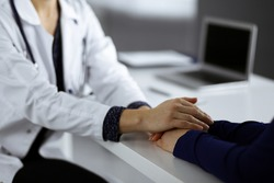 Unknown woman-doctor is reassuring her female patient, close-up. Physician is consulting and giving some advices to a woman. Concepts of medical ethics and trust.