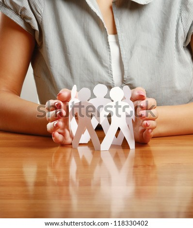 Unknown woman taking care about paper people isolated on grey