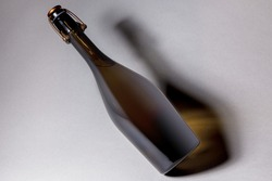 Unlabeled bottle of sparkling wine, with swing top closure, on grey background.