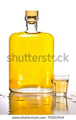 Unlabeled bottle of tequila with a filled shot glass.