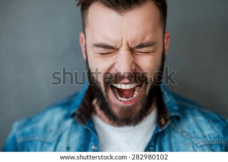 Unleashed emotions. Frustrated young man keeping eyes closed and mouth opened while standing against grey background #282980102