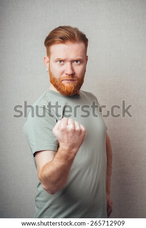 Unleashing his emotions.  Portrait of handsome Young hipster red bearded man wearing orange tshirt and showing his fist with angry face expression while standing against white background