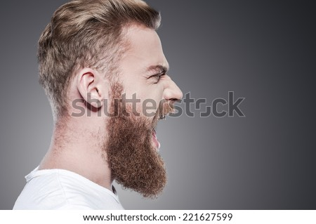 Unleashing his emotions. Side view of furious young bearded man shouting while standing against grey background Stock photo ©