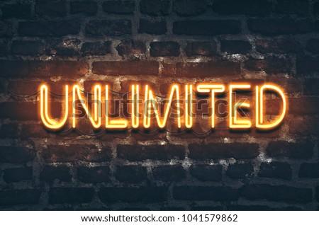 Unlimited neon sign on dark brick wall background