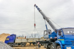 Unloading of building materials by crane at the construction site
