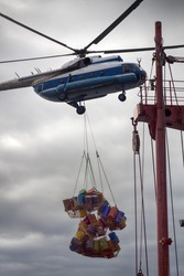 Unloading the expedition ship by ship-based helicopter. Helicopter transport on suspension drums, sling load operation