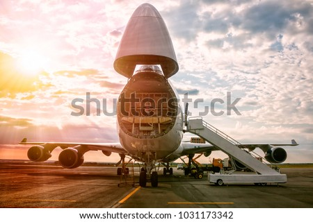 Unloading wide body transport cargo aircraft in the morning sun