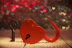 Unlocked heart shaped padlock over abstract Valentines day background