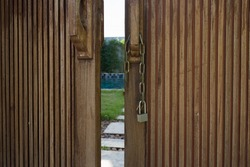 Unlocked metal chain on old wooden doors with green garden and private pool behind.