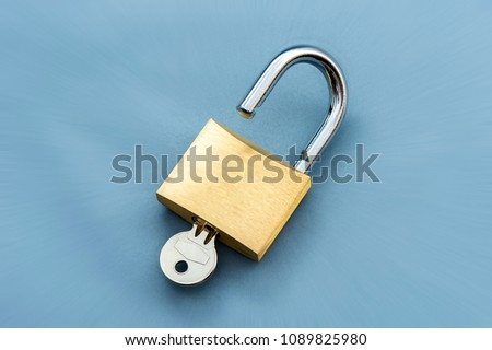 Unlocked Padlock and key on the blue background. - Shutterstock ID 1089825980