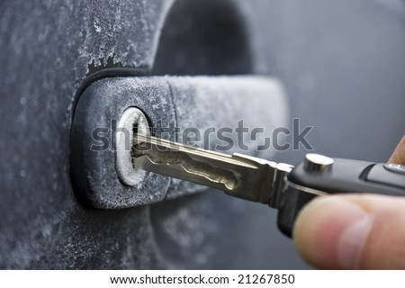 Unlocking a car door on a cold frozen winter morning - stock photo