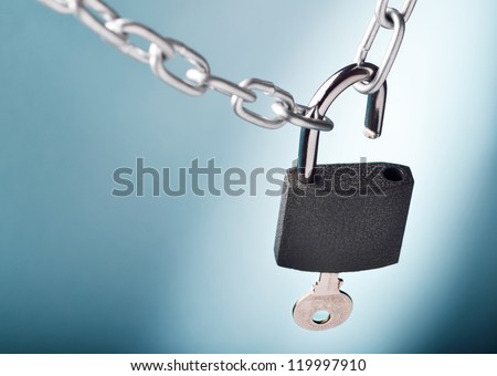 Unlocking a padlock securing two metal chains with blue background