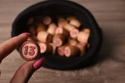 Unlucky number thirteen. Wooden Lotto barrels in black bag on a wooden light table. Table game Bingo. Keg lottery.