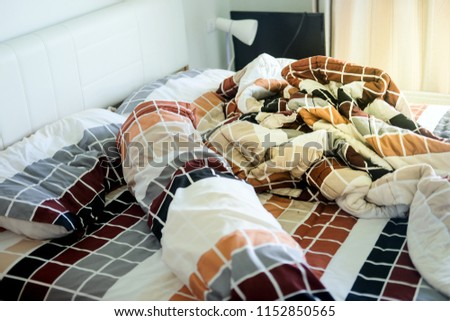 Unmade bed with crumpled bed sheet and pillows after comfort duvet sleep waking up in the morning. #1152850565