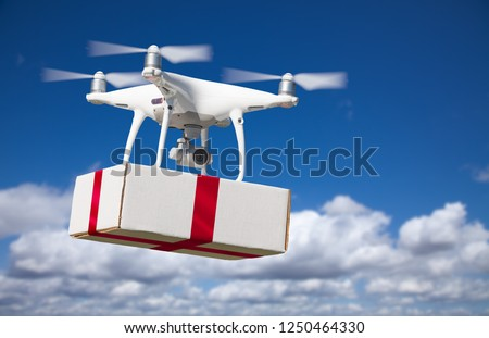Unmanned Aircraft System (UAV) Quadcopter Drone Delivering Box With Red Ribbon