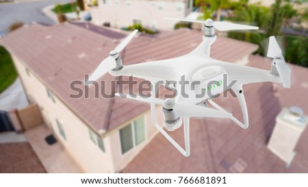 Unmanned Aircraft System (UAV) Quadcopter Drone In The Air Over House Inspecting the Roof.