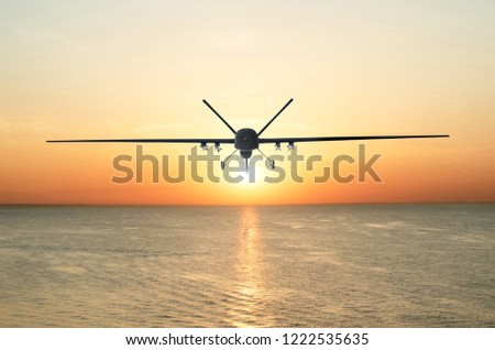 Unmanned military drone patrols the territory at sunset, flying above water surface. The view is straight ahead