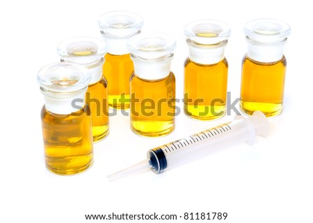 Unmarked glass chemical bottles filled with yellow liquid chemical solution such as illegal sports performance enhancing anabolic steroids and plastic syringe over white