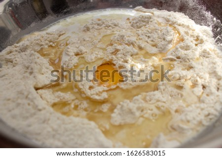 Unmixed ingredients of bread dough: eggs, wheat flour, oil and yeast